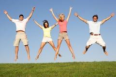 Pares jovenes que saltan en aire Imágenes de archivo libres de regalías