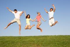 Pares jovenes que saltan en aire Imagen de archivo
