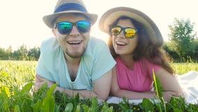 Pares jovenes que se acuestan en hierba y la sonrisa metrajes