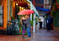 Pares jovenes que se besan debajo del paraguas en la calle Fotos de archivo