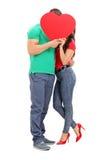 Pares jovenes que se besan detrás de un corazón rojo Imagen de archivo libre de regalías