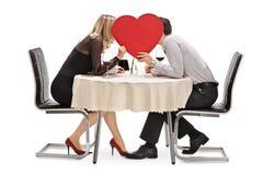 Pares jovenes que se besan detrás de un corazón rojo Foto de archivo libre de regalías