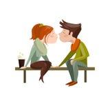 Pares jovenes que se besan en banco Imagen de archivo
