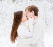 Pares jovenes que se besan en bosque del invierno Foto de archivo