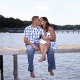 Pares jovenes que se besan en el embarcadero del lago Imagenes de archivo