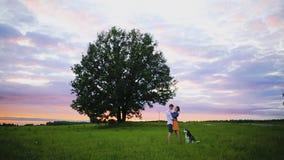 Pares jovenes que se besan en el fondo de una puesta del sol en el campo almacen de video
