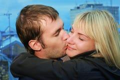 Pares jovenes que se besan en la azotea Imagenes de archivo