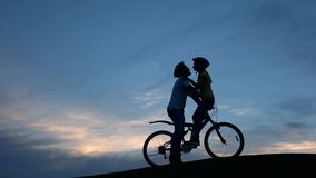 Pares jovenes que se besan en la bicicleta en la puesta del sol almacen de metraje de vídeo
