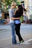 Pares jovenes que se besan en la calle Imagenes de archivo