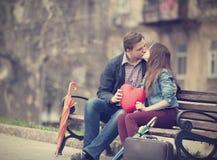 Pares jovenes que se besan en la calle Foto de archivo