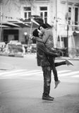 Pares jovenes que se besan en la calle Imagen de archivo