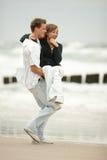 Pares jovenes que se besan en la playa Imágenes de archivo libres de regalías