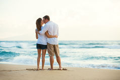 Pares jovenes que se besan en la playa en la puesta del sol Fotografía de archivo