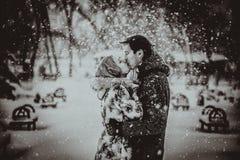 Pares jovenes que se besan en nieve Rebecca 36 Imágenes de archivo libres de regalías