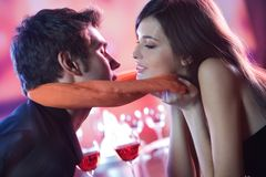 Pares jovenes que se besan en restaurante, celebrando o en d romántica Imagenes de archivo