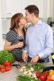 Pares jovenes que se besan en su cocina Fotografía de archivo libre de regalías