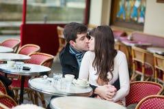 Pares jovenes que se besan en un café al aire libre Imagen de archivo libre de regalías