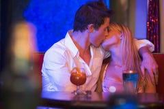 Pares jovenes que se besan en un club nocturno Imagenes de archivo