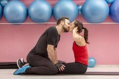 Pares jovenes que se besan en un gimnasio imagen de archivo