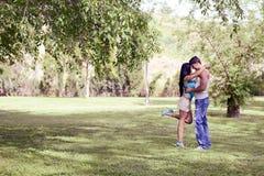 Pares jovenes que se besan en un parque hermoso Imagen de archivo