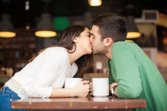 Pares jovenes que se besan en un restaurante Imagen de archivo