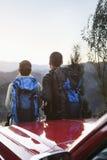 Pares jovenes que se colocan al lado del coche y que miran las montañas Foto de archivo libre de regalías