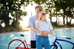 Pares jovenes que se colocan así como las bicicletas rojas y azules por otra parte Muchacho que se coloca con la muchacha hermosa Fotos de archivo libres de regalías