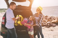 Pares jovenes que se colocan cerca de la bota abierta del coche con las maletas y los bolsos El papá, la mamá y la hija están via fotografía de archivo libre de regalías