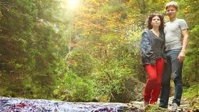 Pares jovenes que se colocan cerca de la cala de la montaña del bosque en el día otoñal sereno; la cámara comienza a enfocar grad almacen de video