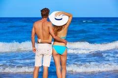 Pares jovenes que se colocan de mirada de la parte posterior de la playa Imágenes de archivo libres de regalías