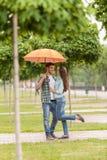 Pares jovenes que se colocan debajo del paraguas en parque Foto de archivo libre de regalías