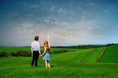 Pares jovenes que se colocan en el campo verde, mujer que muestra su mano en imagenes de archivo
