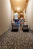 Pares jovenes que se colocan en el pasillo del hotel sobre llegada, buscando el sitio, sosteniendo las maletas Foto de archivo