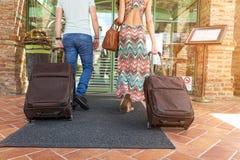 Pares jovenes que se colocan en el pasillo del hotel sobre llegada, buscando el sitio, sosteniendo las maletas Imagen de archivo libre de regalías