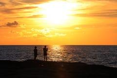 Pares jovenes que se colocan en la orilla y las miradas en el sol poniente Imagen de archivo