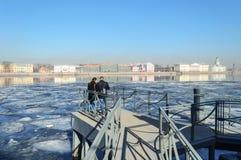Pares jovenes que se colocan en la plataforma de observación en el río de Neva enfrente del terraplén de la universidad en St Pet imágenes de archivo libres de regalías