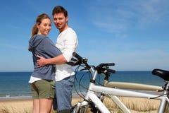 Pares jovenes que se colocan en la playa con las bicis Imágenes de archivo libres de regalías