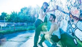 Pares jovenes que se colocan en una pared en un ambiente urbano Fotografía de archivo