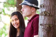 Pares jovenes que se colocan entre árboles, el fluir de la luz del sol Fotos de archivo libres de regalías