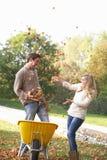 Pares jovenes que se divierten con las hojas de otoño foto de archivo libre de regalías