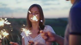 Pares jovenes que se divierten con los fuegos artificiales , los fuegos artificiales están quemando en sus manos almacen de video