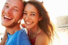 Pares jovenes que se divierten el día de fiesta de la playa junto Foto de archivo libre de regalías