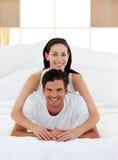 Pares jovenes que se divierten en cama junto Fotografía de archivo