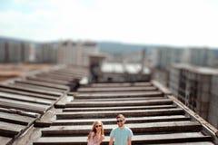 Pares jovenes que se divierten en el tejado gris de la construcción de viviendas i foto de archivo libre de regalías