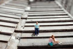 Pares jovenes que se divierten en el tejado gris de la construcción de viviendas i imagen de archivo libre de regalías