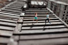 Pares jovenes que se divierten en el tejado gris de la construcción de viviendas i imagenes de archivo
