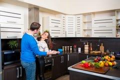 Pares jovenes que se divierten en la cocina Imagen de archivo