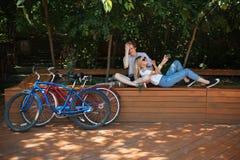 Pares jovenes que se divierten en parque con cerca rojas y azules las bicicletas Muchacho fresco que se sienta en banco en parque Foto de archivo