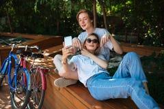 Pares jovenes que se divierten en parque con las bicicletas próximas Muchacho que sienta en banco en parque con la muchacha agrad Fotos de archivo