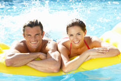 Pares jovenes que se divierten en piscina Fotografía de archivo libre de regalías